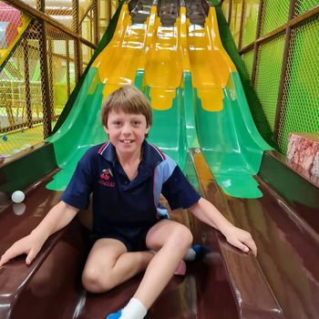 boy at bottom of indoor slide