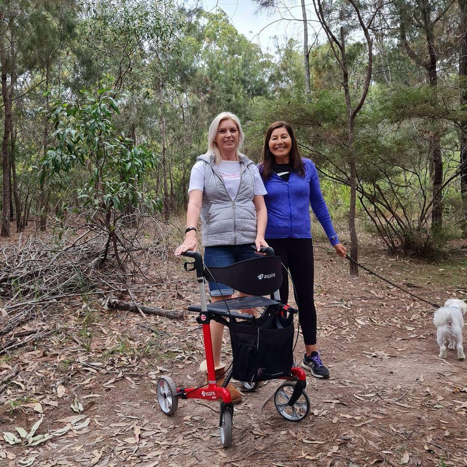 2 ladies walking dog in bush
