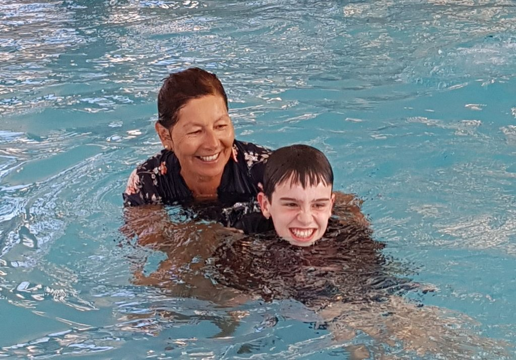 bec and call helping boy in swimming pool